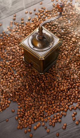 strewed: Old vintage bronze coffee grinder and spilled roasted hot beans with smoke