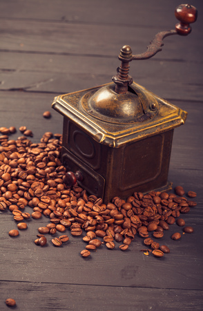 vintage objects: Old vintage bronze coffee mill on spilled roasted hot beans
