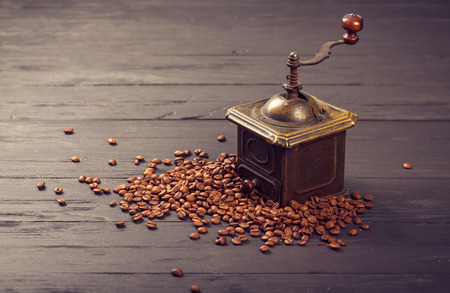 strewed: Old vintage bronze coffee mill on spilled roasted hot beans