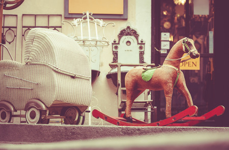 antique chair: Retro baby carriage and toy rocking-horse antique sale Stock Photo
