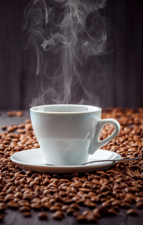 drink coffee: Hot aromatic coffee drink in the white cup with saucer and spoon with beans background