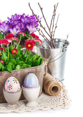 paschal: Easter eggs with spring flowers in basket. Isolated on white background
