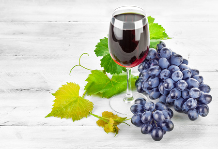 fruit of the spirit: Glass red wine with cluster grapes on wooden board Stock Photo