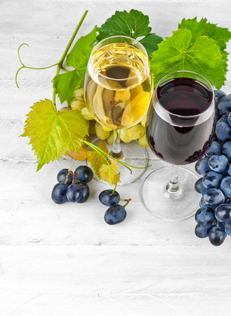 spirituous beverages: Red white wine in wineglass with grapes green willow wooden board