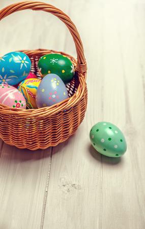 wooden basket: Wicker basket with easter eggs on wooden board