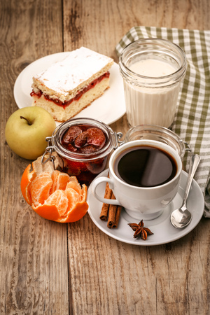 coffee and cake: Morning breakfast with hot coffee and joghurt, fruits tangerines, lemon, apple and sweet cake on wooden board in rustic style
