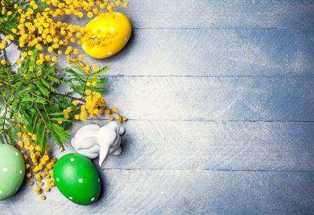 hojas parra: festivo Pascua Bodegón con huevos mimosa rama y conejo en el tablero de madera azul