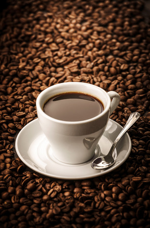 bracing: Black coffee on beans background with spoon