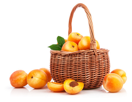 willow fruit basket: Fresh apricot with green leaf in wicker basket still life of fruits, isolated on white background and copyspace Stock Photo