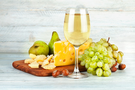 spirituous beverages: Wineglass white wine with fruits nut and cheese parmesan still life on vintage wooden board Stock Photo