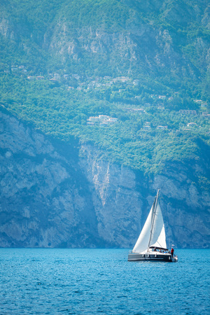 sailer: Sailer boat for voyage floating by waves on Garda lake, Italy. Modern sea travel yacht with sails on blue water surface with high mountains landskape on background