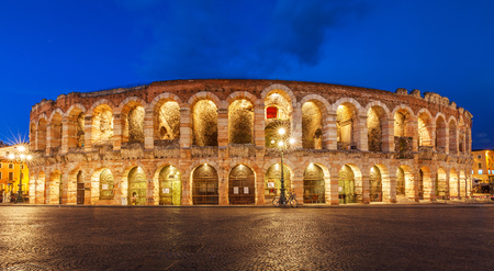 localities: Ancient amphitheater Arena di Verona in Italy, like Coliseum with nighttime illumination and evening blue sky