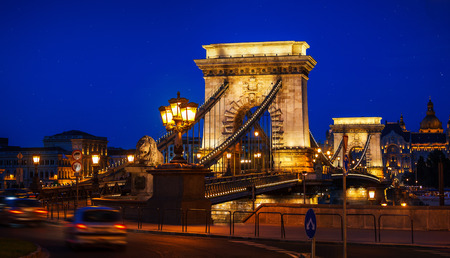 the chain bridge: Ancient Chain bridge on Danube river in Budapest city with lanterns for nighttime backlighting and blue sky