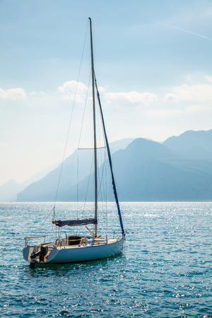 sailer: Sailer at water of lake or sea bay and high blue mountains in misty background landscape Stock Photo