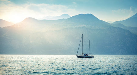 sailer: Landscape panorama with sailer boat ship sailing by lake or sea waves in evening sunset sun sunbeams with high mountains at background. Garda lake, Veneto region, Italy