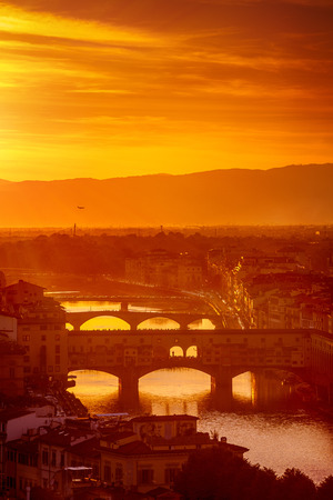 localities: Gold sunset at bridge Ponte Vecchio in Florence old town on Arno river, Italy Stock Photo