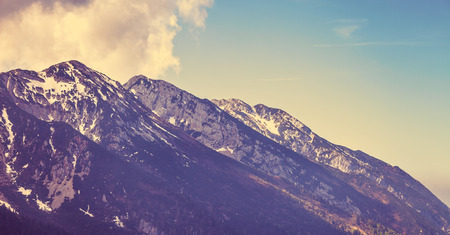 snowbound: Vintage style looking view to rock snowbound Alps mountains summits in clouds.