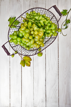 full willow: Fresh green grapes in vintage basket with vine and leaves on wooden board in rustic style