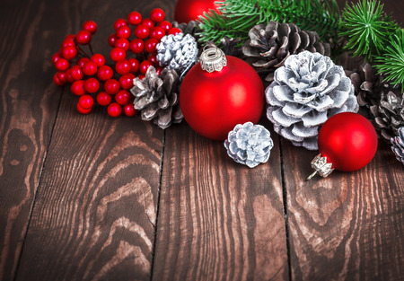 crone: Christmas decoration with red balls pinecone and branch firtree on old wooden board holiday greeting card