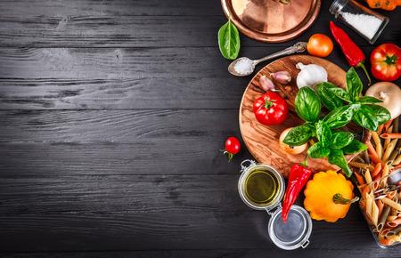 comida italiana: Verduras y especias ingrediente para cocinar comida italiana en negro vieja tarjeta de madera en estilo rústico