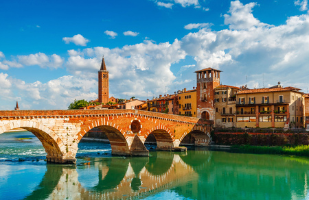localities: Bridge Ponte Pietra in Verona on Adige river, Veneto region, Italy. Sunny summer day panorama and blue sky with clouds. Ancient european terracotta color houses.