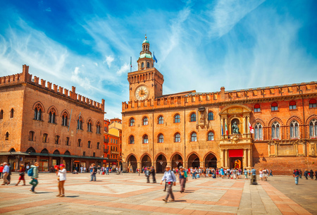 localities: Italy Piazza Maggiore in Bologna old town tower of town hall with big clock and blue sky on background, antique buildings terracotta galleries