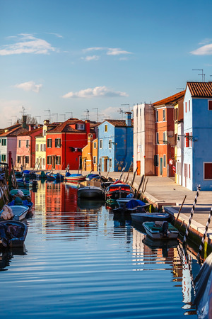 locality: Burano island in Venice, Italy. Motley coloured home coast with boats floating on Channel, blue sky and evening sunset