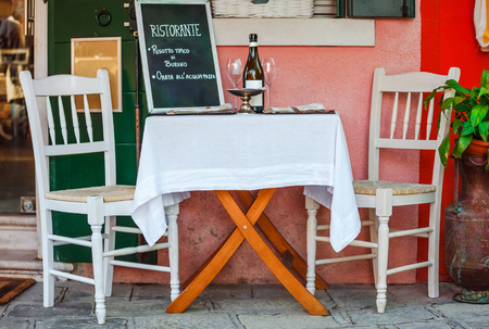 Italian ristorante restaurant served table with white table-cloth and wooden chairs. Old vintage furniture. Wine goblets. Cafe serving for supper in Italy on the street