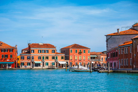 water town: Island Murano in Venice Italy lagoon with dock for boats and coloured old houses antique town at water,