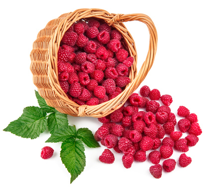 Fresh berries raspberry in wicker basket strewed with green leaves, isolated on white background