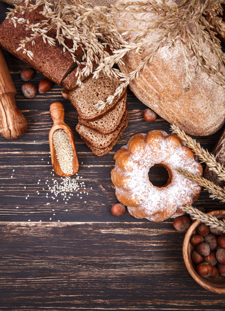 crimp: Fresh crispy breads baking of loaf and sweet donut on old wooden plate in rustic style
