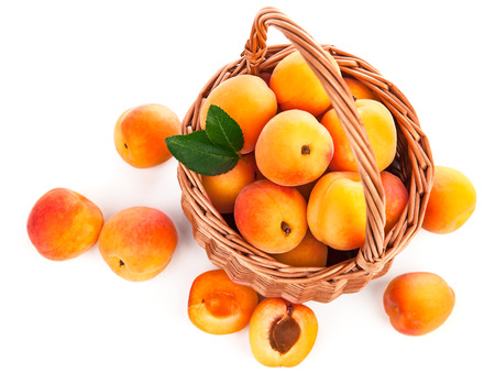 Fresh apricot with green leaf in wicker basket still life of fruits, isolated on white background and copyspace top view