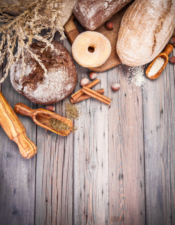 plato del buen comer: Fresh crispy breads baking of loaf and sweet donut on old wooden plate in rustic style copyspace