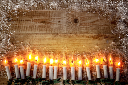 Christmas holiday candles background top view. Candle garland for christmas greeting card, white snow old wooden board rustic style, copyspace under candle fire. Stock Photo