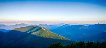 hillock: Sunset sunshine over summits and hills. Panorama landscape of blue Carpathian mountains. Stock Photo