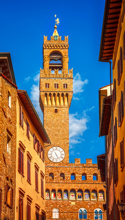 locality: Street view to Tower of Palazzo Vecchio in Florence old town. Italy. Europe. Narrow streets with ancient italian houses and old clock on the towers wall. Famous landmark. Stock Photo