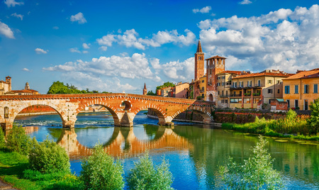 immovable: Panoramic view to Bridge Ponte Pietra in Verona on Adige river, Veneto region, Italy. Sunny summer day panorama and blue dramatic sky with clouds. Ancient european italian terracotta color houses.