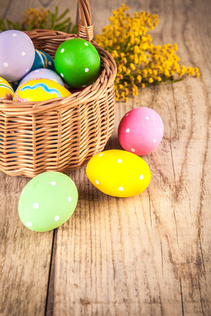 Easter eggs in wicker basket and branch mimosa on wooden board with above copyspace