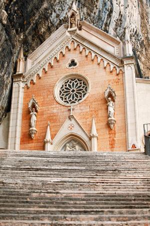 Stone steps of stairs to Ancient Madonna della Corona santuario facade under rocks in high mountains, Veneto region, Italy, famous touristic landmark