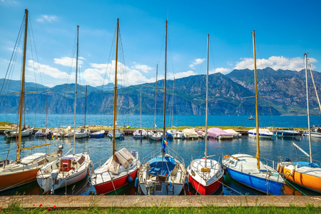 hillock: Sailing boats yachts on Garda lake, Veneto region, Italy. Landscape of marine regatta with floating boats in the harbor with high Alpine mountains background