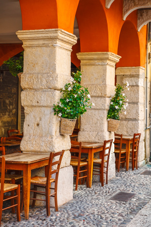 Wooden tables of comfortable outdoor cafe ristorante among ancient columns and archs at Verona streets. Flowers in flowerpots in on poles, front building exterior, Veneto region Italy, Stock Photo