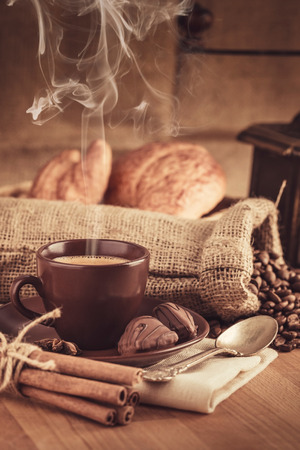 bracing: Cup fragrant hot coffee with bean chocolate sweet and croissant in vintage rustic style cinnamon steam smoke on wooden board for bracing morning breakfast