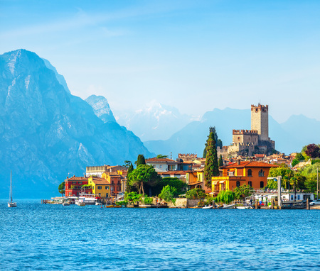 Ancient tower and fortress in old town Malcesine at Garda lake, Veneto region, Italy. High snowbound top mountains on background. Summer landscape with colorful houses and green trees.