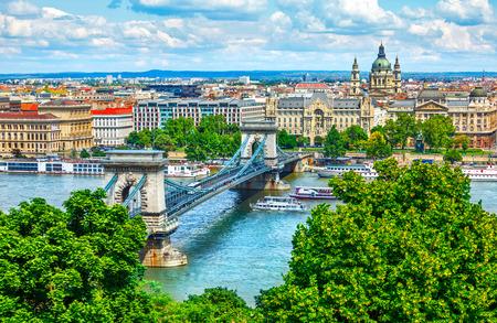 Puente de cadena en el río Danubio en la ciudad de Budapest, Hungría. Panorama del paisaje urbano con edificios antiguos y cúpulas de edificios de ópera Foto de archivo