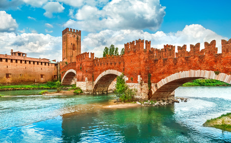 locality: Bridge with archs Castelvecchio over river Adige in Verona Italy brick fortress castle summer landscape sky clouds ancient building famous landmark Stock Photo