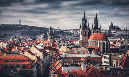 locality: High spires towers of Tyn church in Prague city (Church of Our Lady before Tyn cathedral) urban landscape panorama with red roofs of houses in old town and blue sky with clouds Stock Photo