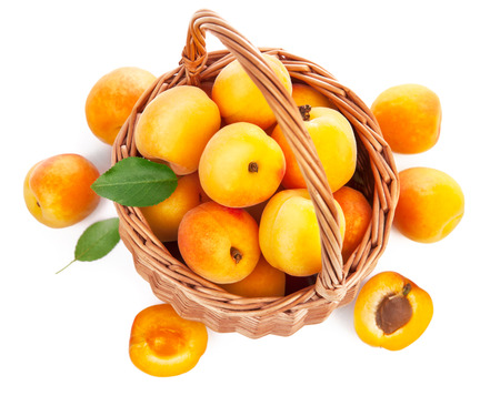 willow fruit basket: Fresh apricot with green leaf in wicker basket still life of fruits, isolated on white background and copyspace top view