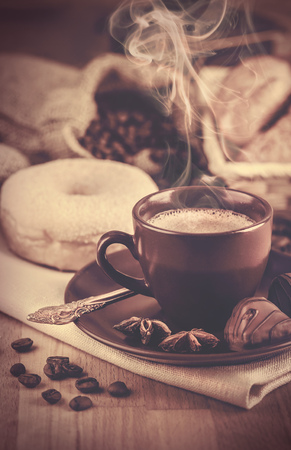 bracing: Cup fragrant hot coffee with bean chocolate sweet and loaf in vintage rustic style cinnamon steam smoke on wooden board for bracing morning breakfast
