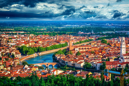 crone: Panorama Italy town Verona and river Adige with dramatic sky urban landscape green tree bridge high tower. Stock Photo