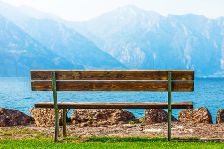 Wooden bench at coast of picturesque lake with blue mountain summits on background. Summer scenic landscape. Calmness, silence and harmony concept. Stock Photo